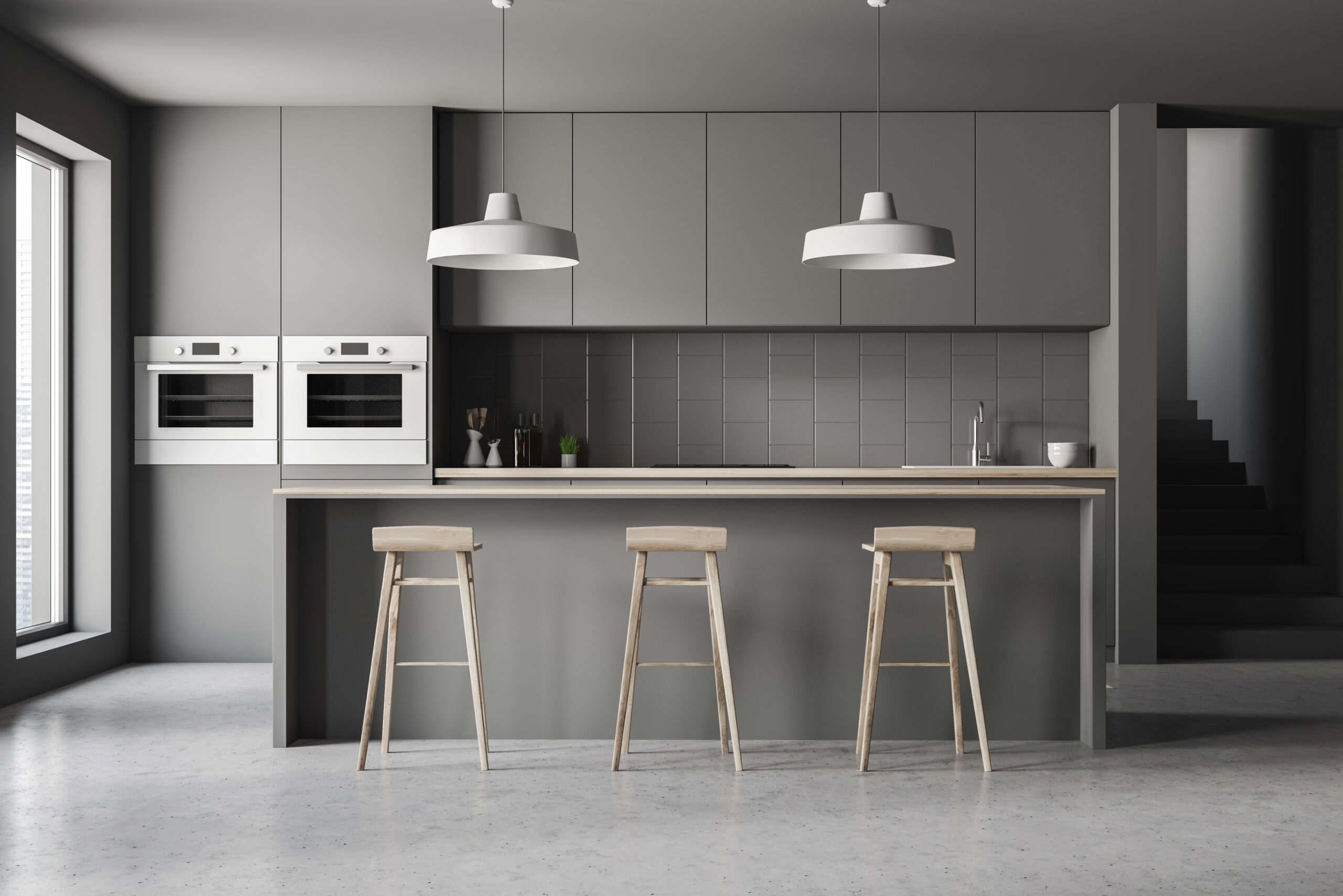 Interior of modern kitchen with gray walls, concrete floor, gray countertops and cupboards and gray and wooden bar with stools. 3d rendering